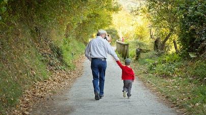 grand-père et son petit fils se promenant sur un chemin bordé d'arbres