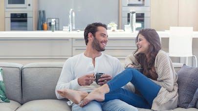 couple souriant sur un canapé
