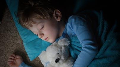 petit garçon dormant avec un ours en peluche dans les bras
