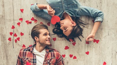 couple allongé sur un parquet autour de coeurs