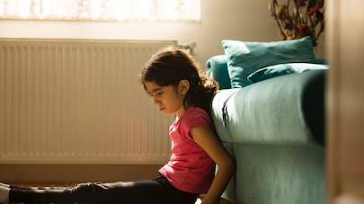 enfant triste assise contre un canapé