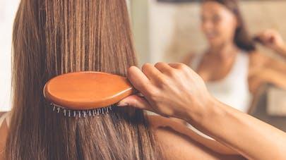 femme se coiffant avec une brosse
