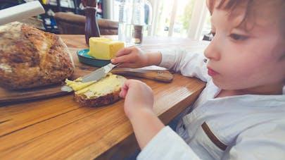garçon se faisant une tartine de pain et beurre
