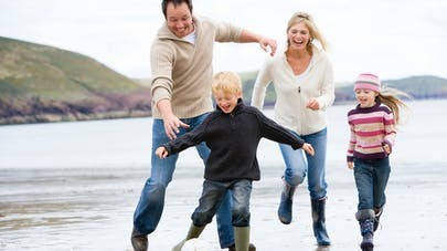 famille jouant au ballon sur la plage