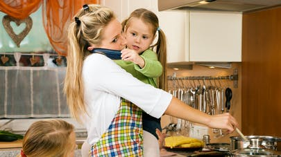 mère stressée avec enfant dans les bras et faisant la cuisine