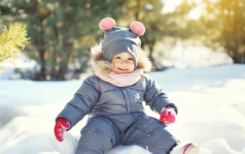 Bébé en combinaison assis dans la neige et souriant