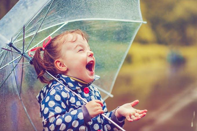 une petite fille crie sous un parapluie