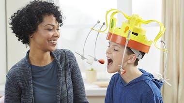 jeu de société Le roi des gourmands avec le casque aux fourchettes sur la tête d'un enfant