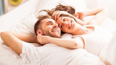 couple souriant sur un lit après l'amour en journée