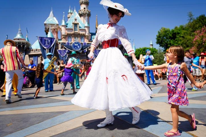 une fillette dans le parc pendant une parade Disney