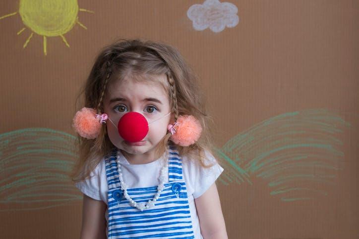 une petite fille avec un nez de clown
