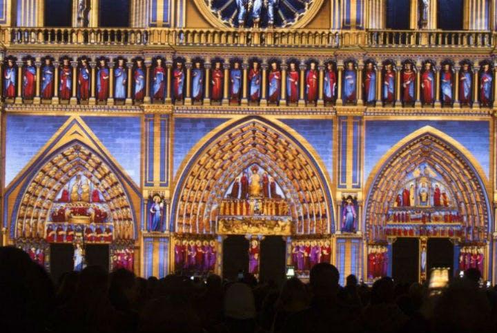La foule devant Notre-Dame de Paris illuminée
