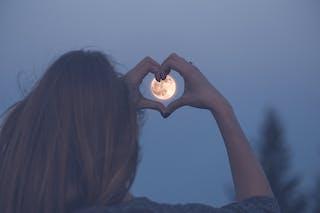 femme un soir de pleine lune fait un coeur avec ses mains