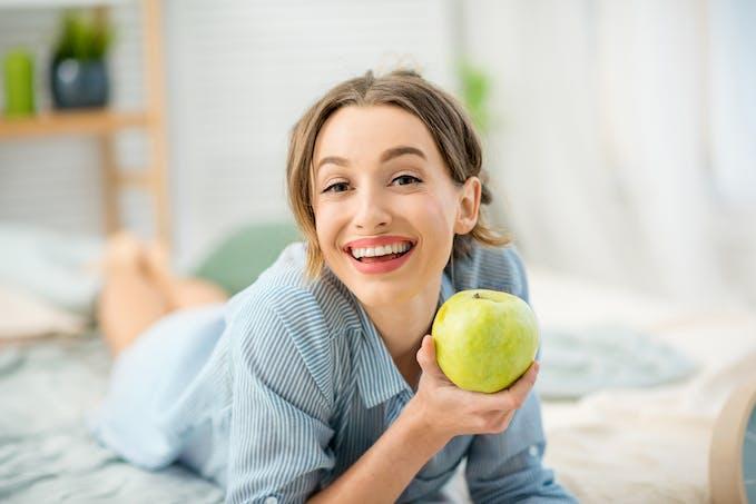 femme sur un lit qui va croquer une pomme