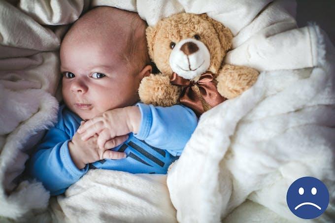 bébé dans un lit avec doudou