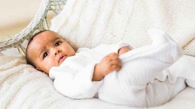 bébé habillé en blanc, couché