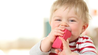 petit garçon blond qui porte un objet à sa bouche