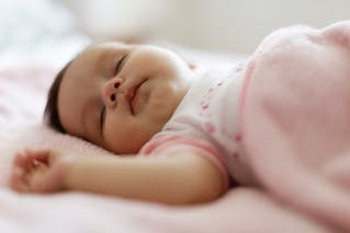 petite fille qui dort dans son couffin