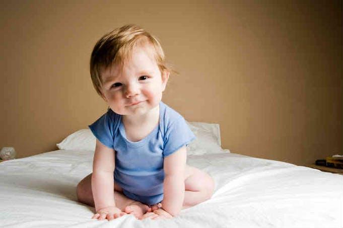 bébé habillé en bleu sur un lit
