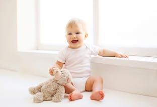 bébé assis avec doudou