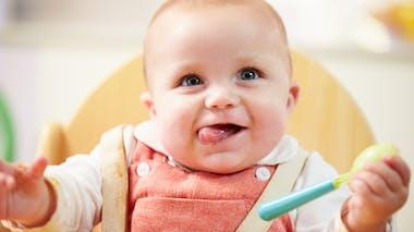bébé une cuillère à la main