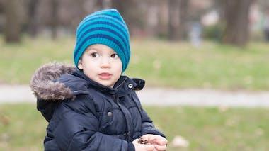 garçon avec bonnet et blouson chaud, dehors