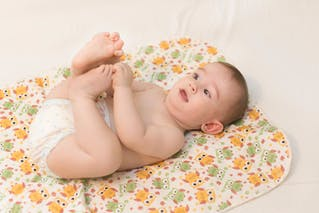 bébé couché qui se touche les pieds