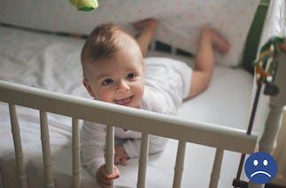 bébé dans un lit à barreaux avec un tour de lit