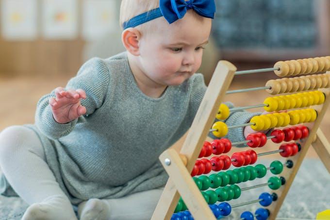 petite fille qui joue avec un boulier