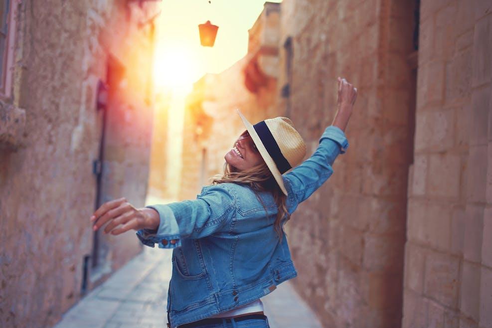 femme qui danse dans une rue ensoleillée
