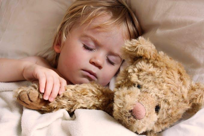 petit garçon au lit avec son ours en peluche