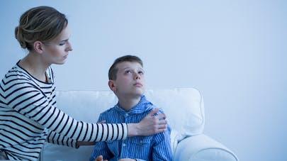 mère et enfant autiste assis sur un canapé