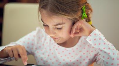 fillette jouant sur une tablette