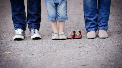 Pieds d'une famille, chaussures de bébé vides