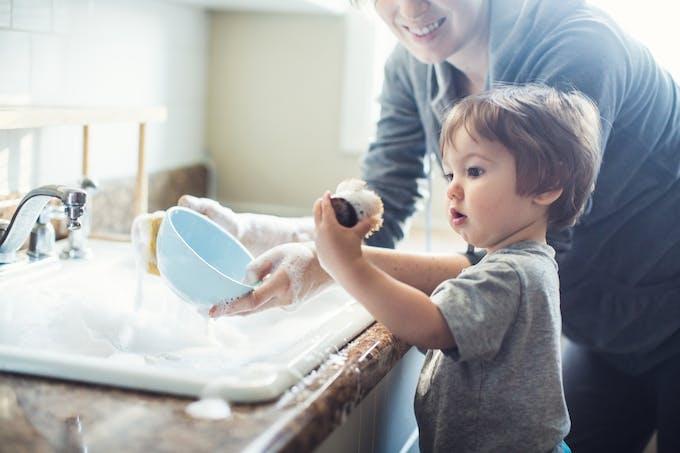 enfant qui fait la vaisselle avec sa mère