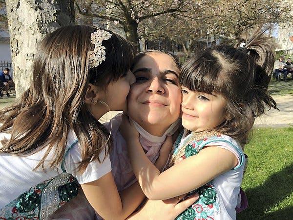 deux petites filles embrassent leur maman