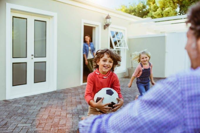 parents et enfants devant une maison