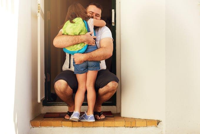 un homme serre une petite fille dans ses bras