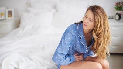 femme assise sur le lit et se tenant le ventre
