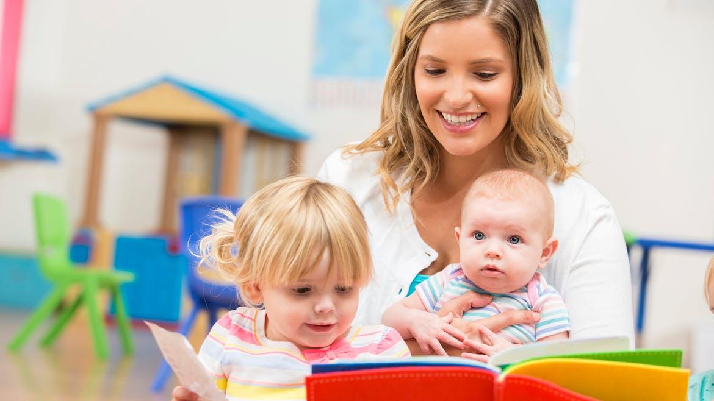 une femme lit un livre à deux bébés