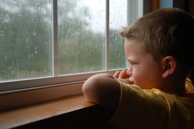 petit garçon regarde la pluie tomber par la fenêtre