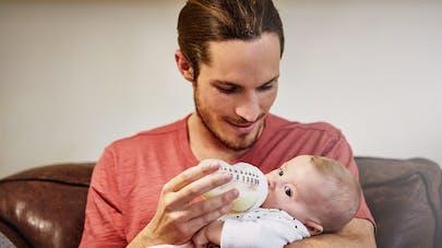 papa donnant un biberon de lait à son bébé