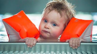 enfant dans une piscine avec des brassards