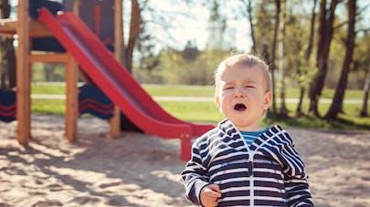 petit garçon qui pleure devant un toboggan