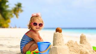 une petite fille joue sur la plage