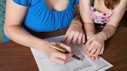 Une maman remplissant un formulaire, avec sa fille à ses côtés