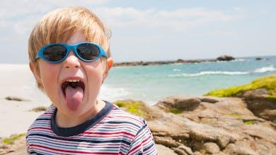 un petit garçon blond à la plage