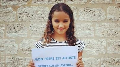 petite fille tient un panneau sur l'autisme