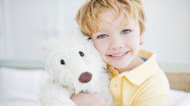 un garçon blond avec une peluche