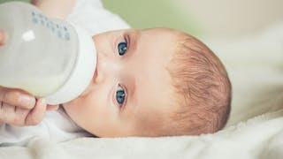 un bébé boit du lait au biberon